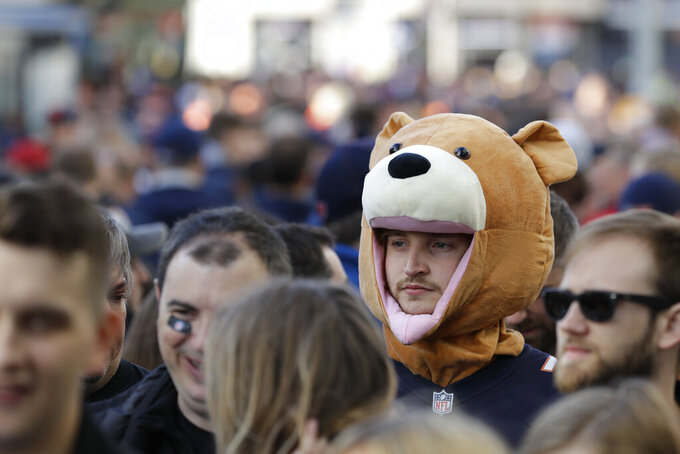CORRECTS STADIUM TO TOTTENHAM HOTSPUR STADIUM INSTEAD OF WEMBLEY STADIUM - A fan waits to enter Tottenham Hotspur Stadium before an NFL football game between the Chicago Bears and the Oakland Raiders, Sunday, Oct. 6, 2019, in London. (AP Photo/Kirsty Wigglesworth)
