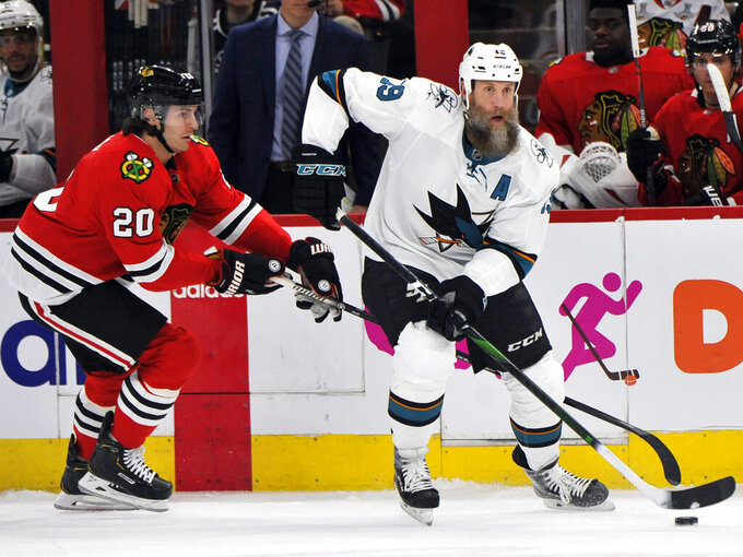 FILE - In this March 11, 2020, file photo, San Jose Sharks' Joe Thornton (19) moves the puck as Chicago Blackhawks' Brandon Saad (20) defends during the first period of an NHL hockey game in Chicago. The Toronto Maple Leafs signed 41-year-old forward Thornton to a one-year, $700,000 contract Friday, Oct. 16, 2020. (AP Photo/Paul Beaty, File)
