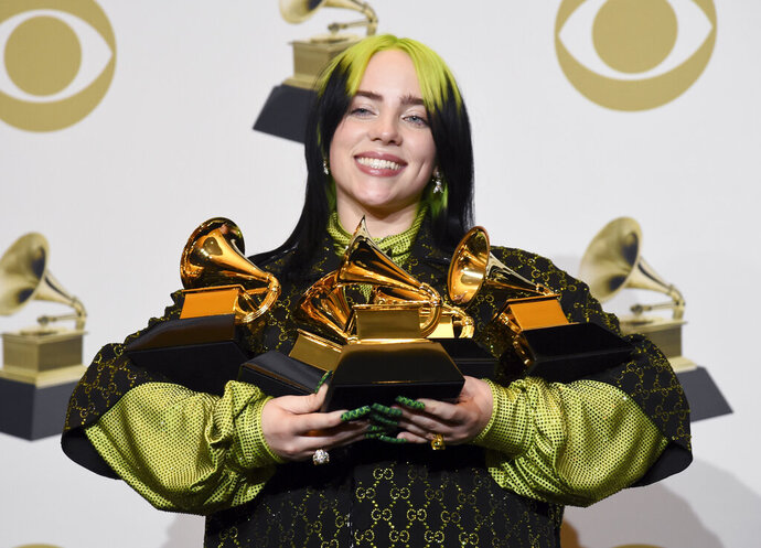 Billie Eilish poses in the press room with the awards for best album and best pop vocal album for