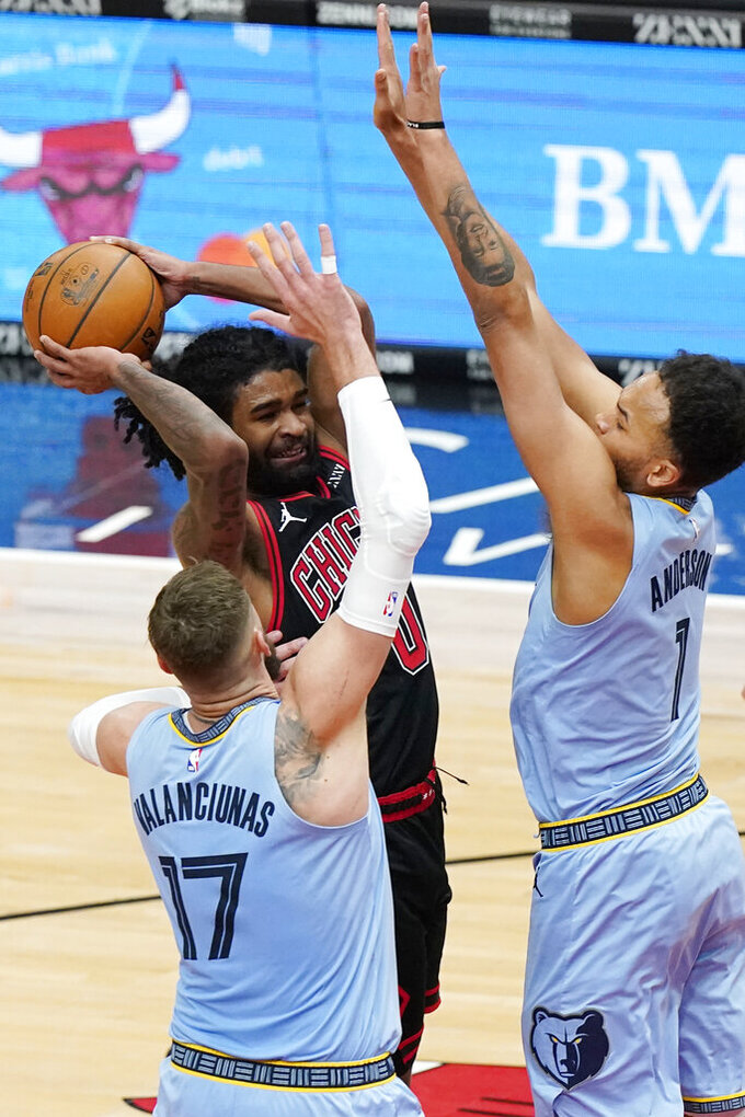 Chicago Bulls guard Coby White, center, drives to the basket as Memphis Grizzlies center Jonas Valanciunas (17) and forward Kyle Anderson guard during the second half of an NBA basketball game in Chicago, Friday, April 16, 2021. (AP Photo/Nam Y. Huh)