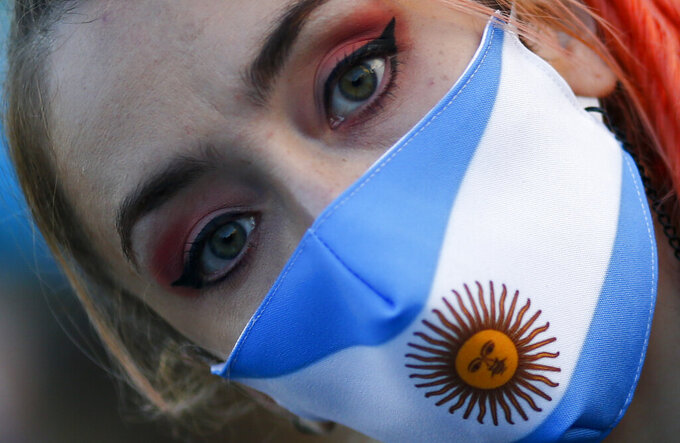 A woman wears a face mask with the colors of the Argentine flag colors during a protest against how the government of President Alberto Fernandez is handling of the new coronavirus pandemic crisis, in Buenos Aires, Argentina, Tuesday, May 25, 2021. (AP Photo/Marcos Brindicci)