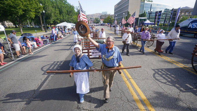 People pull handcarts during the Pioneer Day Parade Friday, July 23, 2021, in Salt Lake City. People in Utah are gathering to celebrate the state's history and recognize early Mormon pioneers who trekked West in search of religious freedom. Pioneer Day is a beloved only-in-Utah holiday every July 24 that features parades, rodeos, fireworks and more. The festivities were canceled last year because of the pandemic.(AP Photo/Rick Bowmer)