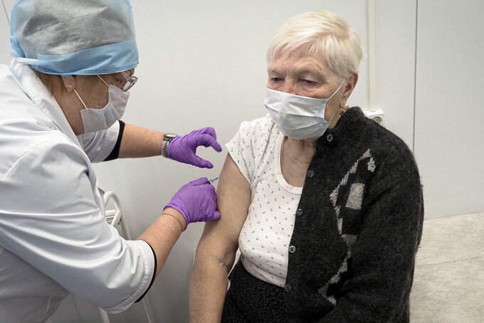 "A Russian medical worker administers a shot of Russia's Sputnik V coronavirus vaccine to Galina Shilova in a local rural medical post in the village of Ikhala in Russia's Karelia region, Tuesday, Feb. 16, 2021. ""When you watch TV and see how people are suffering … you don't want that. You want to live a little longer,"" Shilova said. (AP Photo/Dmitri Lovetsky)"