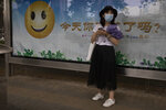 A woman wearing a mask to curb the spread of the new coronavirus waits near a billboard with a smiley face and the slogan