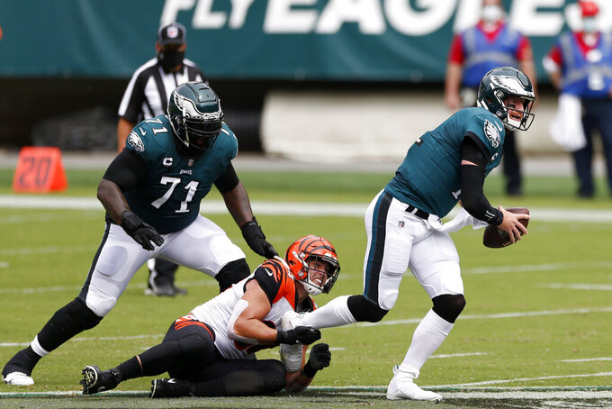 Philadelphia Eagles' Carson Wentz (11) is grabbed by Cincinnati Bengals' Sam Hubbard (94) during the first half of an NFL football game, Sunday, Sept. 27, 2020, in Philadelphia. (AP Photo/Laurence Kesterson)