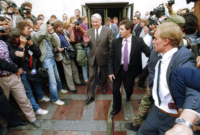 FILE - In this Tuesday, Aug. 20, 1991 file photo, Russian Republic President Boris Yeltsin waves as he makes his way past a throng of photographers outside the Russian Federation building in Moscow, Russia. Yeltsin, who arrived at his office shortly after, climbed atop a tank to make a passionate speech urging to people to defy the coup. I spent the chaotic day taking shots of protesters around Yeltsin's headquarters and running to the office to have my films developed. (AP Photo/Alexander Zemlianichenko, File)