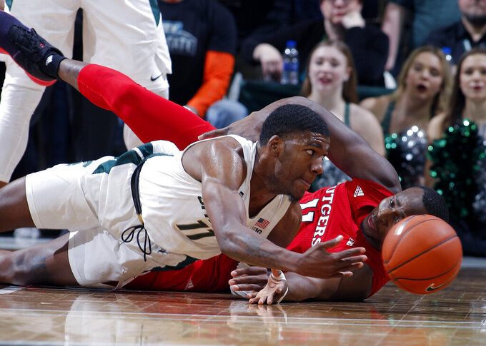 Michigan State's Aaron Henry, left, and Rutgers' Mamadou Doucoure hit the floor as they scramble for a loose ball during the first half of an NCAA college basketball game, Sunday, Dec. 8, 2019, in East Lansing, Mich. (AP Photo/Al Goldis)