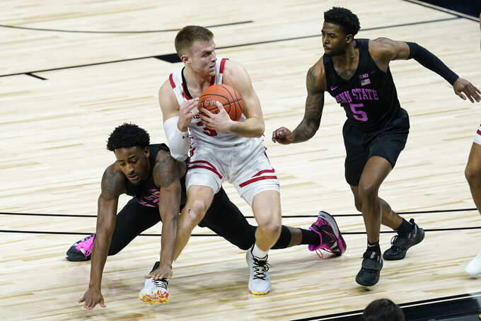 Wisconsin's Brad Davison (34) recovers a loose ball against Penn State's Izaiah Brockington (12) and Jamari Wheeler (5) during the first half of an NCAA college basketball game at the Big Ten Conference tournament, Thursday, March 11, 2021, in Indianapolis. (AP Photo/Darron Cummings)