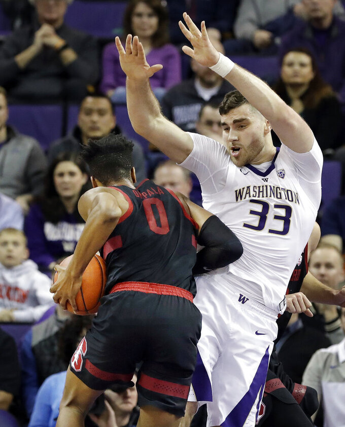Washington's Sam Timmins (33) defends against Stanford's KZ Okpala (0) during the first half of an NCAA college basketball game Thursday, Jan. 17, 2019, in Seattle. (AP Photo/Elaine Thompson)