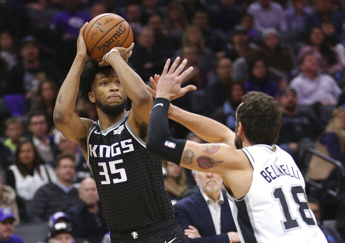 Sacramento Kings forward Marvin Bagley III, left, shoots against San Antonio Spurs guard Marco Belinelli during the first quarter of an NBA basketball game, Monday, Feb. 4, 2019, in Sacramento, Calif. The Kings won 127-112. (AP Photo/Rich Pedroncelli)