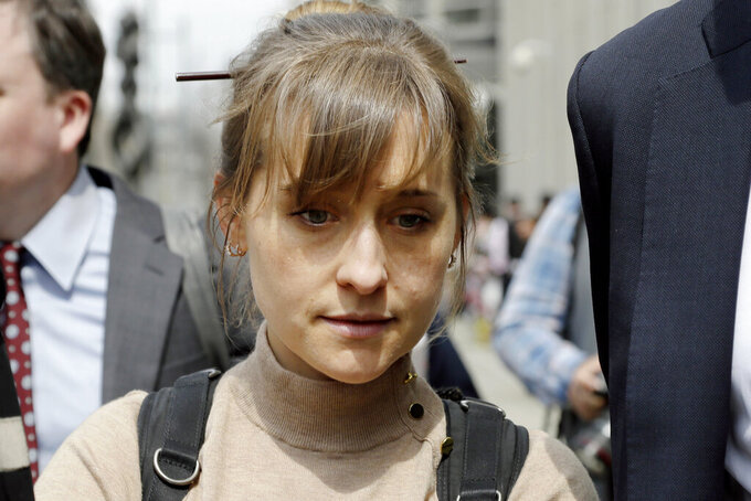 FILE-  In this April 8, 2019 file photo, actor Allison Mack leaves Brooklyn federal court in New York after pleading guilty to racketeering charges in a case involving a cult-like group based in upstate New York called NXIVM.  Mack, who played a key role in the cultlike group NXIVM, has surrendered to a California prison to serve her sentence in a New York case against the group's spiritual leader. (AP Photo/Mark Lennihan, File)