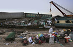 Railway workers use crane to clear the track at the track at the site of a train collision in the Ghotki district, southern Pakistan, Monday, June 7, 2021. An express train barreled into another that had derailed in Pakistan before dawn Monday, killing dozens of passengers, authorities said. More than 100 were injured, and rescuers and villagers worked throughout the day to search crumpled cars for survivors and the dead. (AP Photo/Fareed Khan)