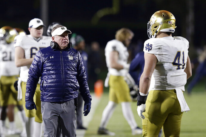 Notre Dame head coach Brian Kelly speaks with Notre Dame defensive lineman Kurt Hinish (41) during the first half of an NCAA college football game against Duke in Durham, N.C., Saturday, Nov. 9, 2019. (AP Photo/Gerry Broome)