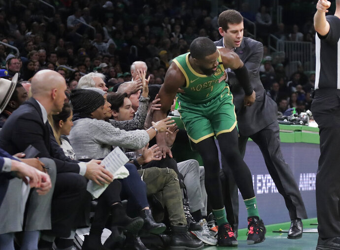 Boston Celtics coach Brad Stevens grabs guard Jaylen Brown to keep him from falling among fans near the bench during the second quarter of the team's NBA basketball game against the Golden State Warriors, Thursday, Jan. 30, 2020, in Boston. (AP Photo/Elise Amendola)
