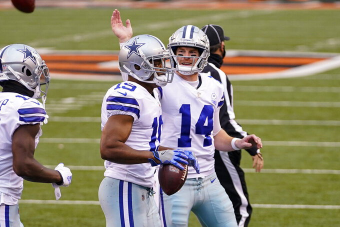 Dallas Cowboys quarterback Andy Dalton (14) celebrates a touchdown throw with wide receiver Amari Cooper (19) in the first half of an NFL football game against the Cincinnati Bengals in Cincinnati, Sunday, Dec. 13, 2020. (AP Photo/Bryan Woolston)