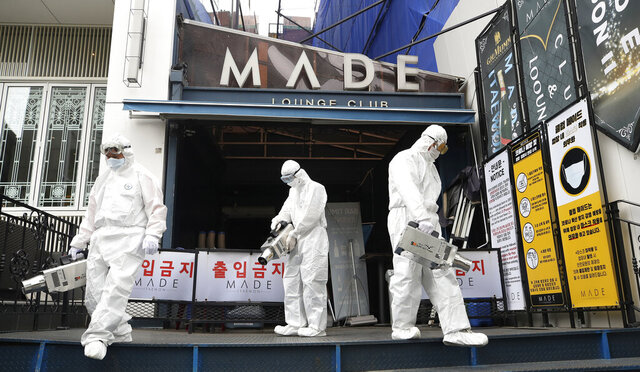 Workers spray disinfectant in front of the MADE, a major club in the international tourist district of Itaewon, in Seoul, South Korea, on May 12, 2020. As South Korea significantly relaxes its rigid social distancing rules as a result of waning coronavirus cases, the world is paying close attention to whether it can return to something that resembles normal - or face a virus resurgence. Already, a mini-outbreak linked to nightclubs in Seoul has tested South Korea's widely praised method for dealing with the disease _ essentially a combination of rapid tracing, testing and treatment, along with stringent social distancing practices. (Lim Hun-jung/Yonhap via AP)