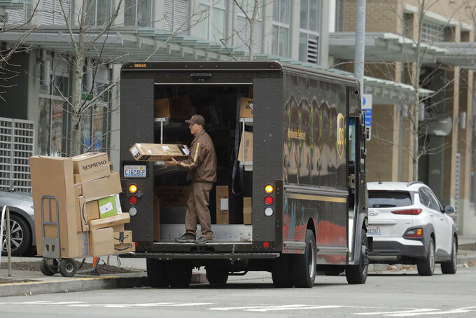 FILE - In this Thursday, March 26, 2020 file photo, a United Parcel Service driver loads boxes during a delivery in downtown Seattle. Amid the coronavirus outbreak, UPS and FedEx have stopped requiring signatures for packages. (AP Photo/Ted S. Warren)