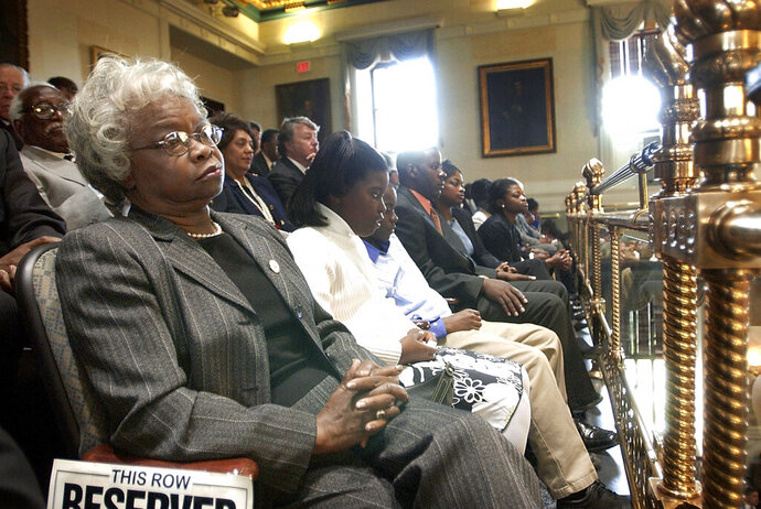 FILE - In this April 10, 2007, file photo, Family members of U.S. House Majority Whip Jim Clyburn, from left, wife Emily Clyburn, grandchildren Sydney and A.C. Reed, son-in-law Walter Reed, daughters Jennifer and daughter Angela, listen as he addresses a joint session of the South Carolina Legislature in Columbia, S.C. Emily Clyburn, the wife of House Majority Whip Jim Clyburn of South Carolina who helped raise millions of dollars to help students attend the alma mater they shared, died in Columbia on Thursday morning, Sept. 19, 2019. according to the congressman's office. She was 80. (Tim Dominick/The State via AP, File)