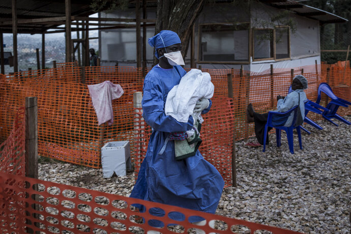 In this photo taken Sunday, Nov. 4, 2018 and made available Tuesday, Dec. 4, 2018, a caretaker already cured of Ebola is seen carrying a four day old baby suspected of having Ebola into a Medecins Sans Frontieres (MSF) supported Ebola treatment centre in Butembo, Congo. Congo's deadly Ebola outbreak is now the second largest in history, behind the devastating West Africa outbreak that killed thousands a few years ago, according to the World Health Organization. (John Wessels/Medecins Sans Frontieres via AP)