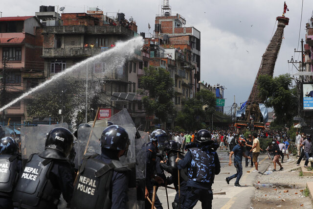 Nepalese protesters defying a government coronavirus lockdown to take part in a religious festival clash with riot police, in Lalitpur, Nepal, Thursday, Sept. 3, 2020. A 5-story-high chariot holding a statue of the deity Rato Machindranath was built but parked for months because of government orders not hold the annual festival due to fear over the spread of the coronavirus. The statue is normally pulled around the city for a month. Police officers in riot gear blocked the protesters when they moved the chariot, dousing them with water cannons. (AP Photo/Niranjan Shrestha)