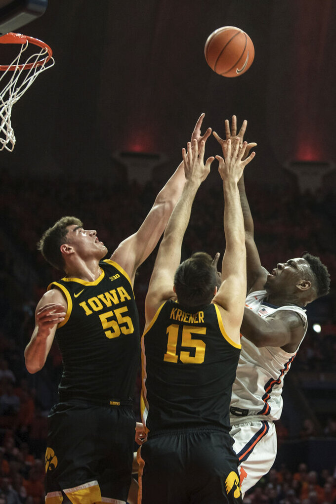 Illinois' Kofi Cockburn,right, shoots as Iowa's Luca Garza (55) and Ryan Kriener (15) defend in the first half of an NCAA college basketball game Sunday, March 8, 2020, in Champaign, Ill. (AP Photo/Holly Hart)