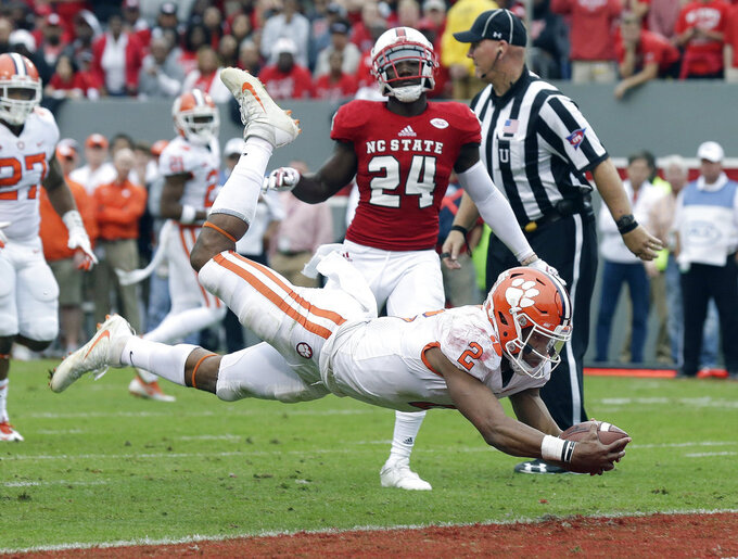 Clemson quarterback Kelly Bryant (2) dives into the end zone for a touchdown while North Carolina State's Shawn Boone (24) looks on during the first half of an NCAA college football game in Raleigh, N.C., Saturday, Nov. 4, 2017. (AP Photo/Gerry Broome)