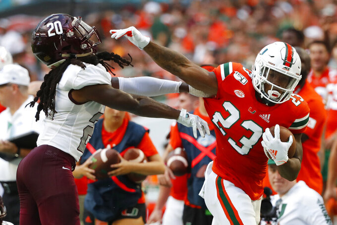 Bethune-Cookman cornerback Trevor Merritt (20) attempts to stop Miami running back Cam'Ron Harris (23) during the first half of an NCAA college football game Saturday, Sept. 14, 2019, in Miami Gardens, Fla. (AP Photo/Wilfredo Lee)