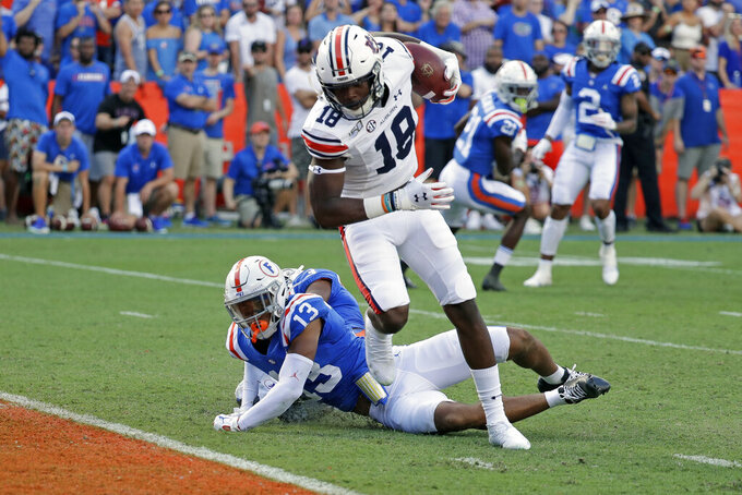 Auburn wide receiver Seth Williams (18) runs to the end zone past Florida defensive back Donovan Stiner (13) for a touchdown on a 32-yard pass play during the first half of an NCAA college football game, Saturday, Oct. 5, 2019, in Gainesville, Fla. (AP Photo/John Raoux)