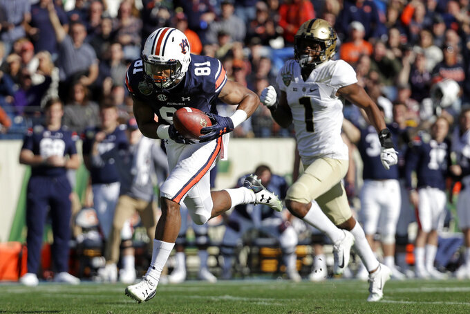 Auburn wide receiver Darius Slayton (81) catches a pass ahead of Purdue cornerback Dedrick Mackey (1) as Slayton scores a touchdown on a 74-yard pass completion in the first half of the Music City Bowl NCAA college football game Friday, Dec. 28, 2018, in Nashville, Tenn. (AP Photo/Mark Humphrey)