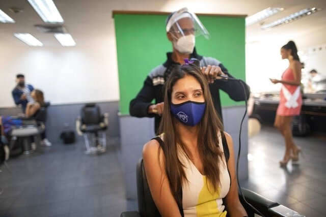 A beauty pageant contestant, wearing a protective face mask issued by the Miss Venezuela beauty pageant, watches as her hair is styled in a Venevision television station dressing room, in Caracas, Venezuela, Friday, Sept. 18, 2020. Quarantine rules and social distancing has forced the contestants to train at home and online with limited access to the venue itself where strict measures are in place. The pageant is due to take place on Sept. 24. (AP Photo/Ariana Cubillos)