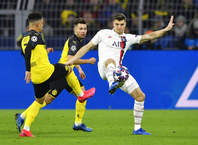 FILE - In this Tuesday, Feb. 18, 2020 file photo, Dortmund's Jadon Sancho, left, and PSG's Thomas Meunier duels for the ball during the Champions League round of 16 first leg soccer match between Borussia Dortmund and Paris Saint Germain in Dortmund, Germany. Borussia Dortmund signed right back Thomas Meunier from Paris Saint-Germain on Thursday June 25, 2020. (AP Photo/Martin Meissner, File)