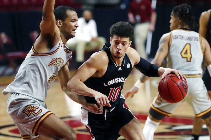 Louisville's Samuell Williamson (10) drives past Boston College's Steffon Mitchell (41) during the first half of an NCAA college basketball game, Saturday, Jan. 2, 2021, in Boston. (AP Photo/Michael Dwyer)