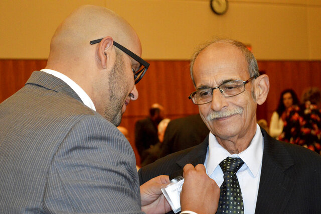 State Rep. Javier Martínez, D-Albuquerque, pins a badge of his father, Javier Martínez, Sr., of Juarez, Mexico, before the start of the New Mexico legislative session in Santa Fe, N.M. on Tuesday, Jan. 21, 2020. New Mexico's Democrat-led Legislature is looking for new ways to bolster a lagging public education system and open up new economic opportunities by legalizing recreational marijuana and providing tuition-free college education, as a 30-day legislative session began Tuesday. (AP Photo/ Russell Contreras)