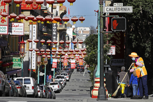 A masked worker cleans a street Friday, Jan. 31, 2020, in the Chinatown district in San Francisco. As China grapples with the growing coronavirus outbreak, Chinese people in California are encountering a cultural disconnect as they brace for a possible spread of the virus in their adopted homeland. (AP Photo/Ben Margot)