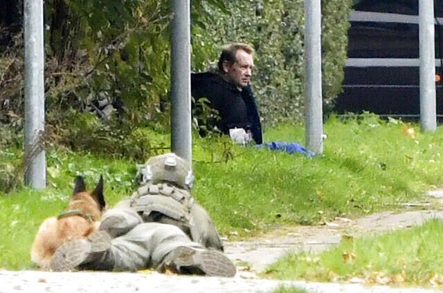 A police office watches Peter Madsen as he sits on the side of a road after being apprehended following a failed escape attempt in Albertslund, Denmark, Tuesday Oct. 20, 2020. The self-taught Danish engineer, who was convicted of torturing and murdering a Swedish journalist on his homemade submarine in 2017 before dismembering her body and dumping it at sea, on Tuesday was captured after attempted prison escape outside the suburban Copenhagen jail where he is serving life-time sentence. (Nils Meilvang/Ritzau Scanpix via AP)