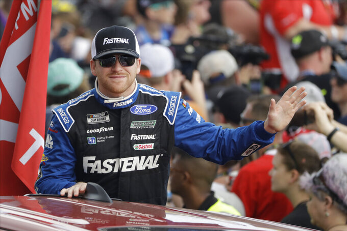 FILE - Chris Buescher gestures during a parade lap before the NASCAR Daytona 500 auto race at Daytona International Speedway in Daytona Beach, Fla., in this Sunday, Feb. 16, 2020, file photo. Roush Fenway Racing on Wednesday, May 19, 2021, announced a contract extension with both driver Chris Buescher and longtime sponsor Fastenal. The deal with Fastenal was extended through the 2024 season. (AP Photo/Chris O'Meara, File)