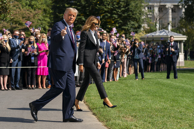 As a crowd of interns and others gathers behind them, President Donald Trump gives the thumbs-up as he and first lady Melania Trump walk to board Marine One at the White House, Tuesday, Sept. 29, 2020, in Washington, for the short trip to Andrews Air Force Base en route to Cleveland for first debate against Democrat Joe Biden. (AP Photo/Carolyn Kaster)