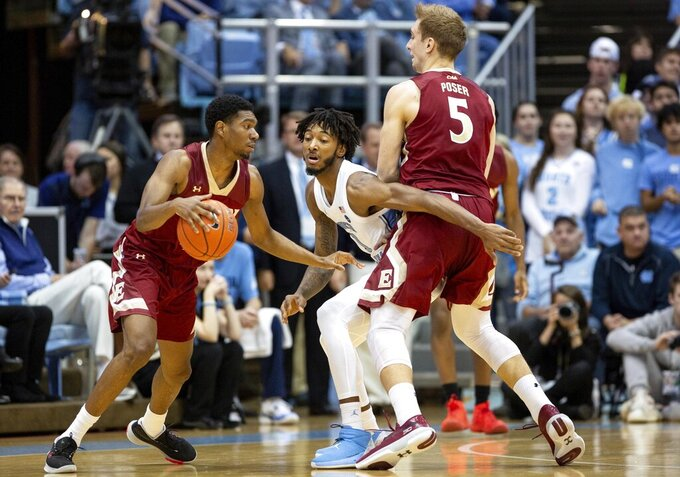 Elon's Marcus Sheffield II, left, dribbles past a pick set by Elon's Federico Poser (5) against North Carolina's Leaky Black (1) during the first half of an NCAA college basketball game in Chapel Hill, N.C., Wednesday, Nov. 20, 2019. (AP Photo/Ben McKeown)