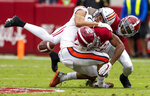 The ball comes out as Auburn wide receiver Anthony Schwartz is tackled and downed by Alabama defensive back Daniel Wright and defensive back Josh Jobe (28) during an NCAA college football game Saturday, Nov. 28, 2020, in Tuscaloosa, Ala. (Mickey Welsh/The Montgomery Advertiser via AP)