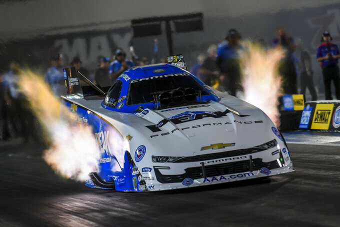 In this photo provided by the NHRA, Funny Car points leader John Force races to the provisional No. 1 position in his first-round qualifying run in his PEAK Chevrolet Camaro SS at the DeWalt NHRA Carolina Nationals at zMAX Dragway in Concord, N.C., Friday, Sept. 17, 2021 (Richard H. Shute/NHRA via AP)