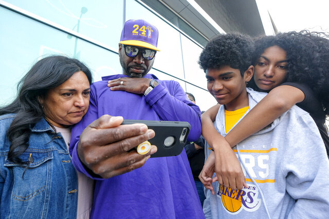 Fans watch the live stream of a public memorial for Kobe Bryant and his daughter, Gianna, outside the Staples Center in Los Angeles, Monday, Feb. 24, 2020. (AP Photo/Ringo H.W. Chiu)