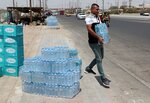 In this Sunday, July, 21, 2019, a man buys drinking water in Basra, southeast of Baghdad, Iraq. A leading rights group says Iraq's government is failing to properly address underlying causes for an ongoing water crisis in the country's south. A report released on Monday by Human Rights Watch on chronic water shortages and pollution in Iraq's Basra province says authorities continue to allow activities that pollute the province's water resources despite the health risks to residents. (AP Photo/Nabil al-Jurani)