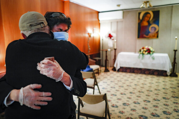 Leonardo Cabaña cries in the arms of his friend Raphael Benevides beside the casket of his father, Héctor Miguel Cabaña, who died of COVID-19 before the funeral home service led by the Rev. Fabian Arias, Monday, May 11, 2020, in the Brooklyn borough of New York. In hard-hit New York City, the coronavirus outbreak has taken a particularly heavy toll on Hispanic communities. (AP Photo/John Minchillo)