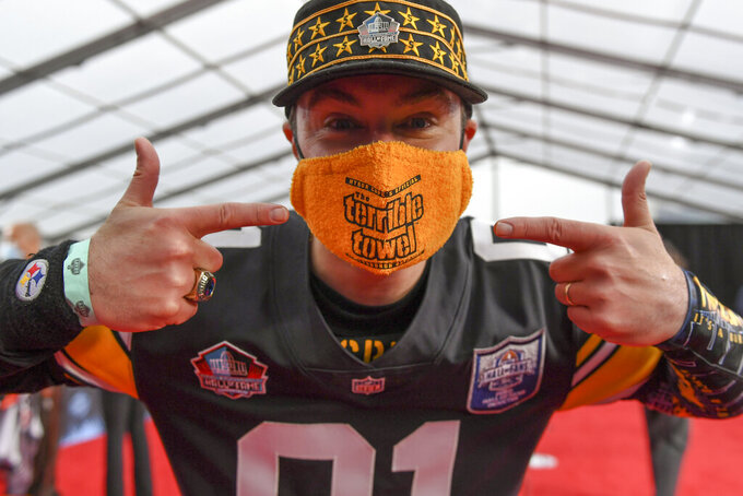 """CORRECTS NAME OF PERSON TO RICK HOLMAN, INSTEAD OF DAVID DERMER- Rick Holman, a fan of the Pittsburgh Steelers, points out his """"Terrible Mask"""" as he waits for potential draftees to appear on the fed carpet at the Rock & Roll Hall of Fame before the NFL football draft, Thursday, April 29, 2021, in Cleveland. (AP Photo/David Dermer, Pool)"""