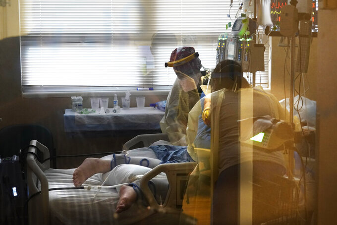 FILE - In this Aug. 18, 2021, file photo, medical staff tend to a patient with coronavirus, on a COVID-19 ward inside the Willis-Knighton Medical Center in Shreveport, La. COVID-19 deaths and cases in the U.S. have climbed back to where they were over the winter, wiping out months of progress and potentially bolstering President Joe Biden's case for sweeping new vaccination requirements. (AP Photo/Gerald Herbert, File)