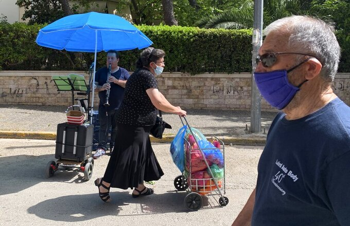 Street musician Roberto Selfos of Albania plays his clarinet as people wearing face masks to prevent the spread of coronavirus, shop at an open-air fruit and vegetable market in Athens, Friday, May 7, 2021.  Greece's vaccination drive has been picking up pace as the country has administered just over 3.4 million vaccines. (AP Photo/Thanassis Stavrakis)