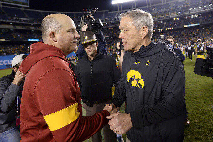 Southern California coach Clay Helton, left, and Iowa coach Kirk Ferentz shake hands following the Holiday Bowl NCAA college football game Friday, Dec. 27, 2019, in San Diego. Iowa won 49-24. (AP Photo/Orlando Ramirez)