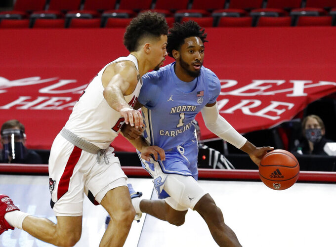 North Carolina's Leaky Black (1) drives past N.C. State's Devon Daniels (24) of an NCAA college basketball game in Raleigh, N.C., Tuesday, Dec. 22, 2020. (Ethan Hyman/The News & Observer via AP)