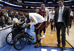 FILE - In this March 15, 2018, file photo, Sister Jean Dolores Schmidt, left, greets members of the Loyola-Chicago basketball team as they walk off the court after a win over Miami in a first-round game at the NCAA men's college basketball tournament in Dallas, This season's tournament, like all before them, would've been filled with dozens of legends in the making and diamonds in the rough _ with teams that overcame adversity to get this far and superfans who inspired the country every bit as much as their team. (AP Photo/Tony Gutierrez, File)