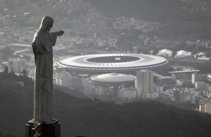 FILE - This May 13, 2014 file photo shows Maracana stadium behind the Christ the Redeemer statue in Rio de Janeiro, Brazil. Brazil will host Copa America for the second consecutive time after Colombia and Argentina were stripped of hosting rights for the tournament, according to the South American soccer body CONMEBOL on Monday, May 31, 2021, hours after it ruled out Argentina amid an increase in COVID-19 cases in the country. Colombia was removed as co-host on May 20 as street protests against President Iván Duque rocked the nation. (AP Photo/Felipe Dana, File)